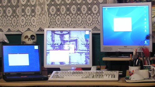[Three computers, three screens, one keyboard and one mouse]