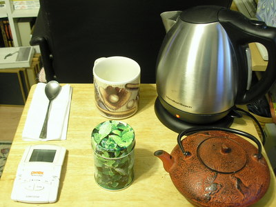 [Clockwise, starting at noon—tea cup, electric kettle, tea pot, loose leaf green tea, timer, tea spoon]