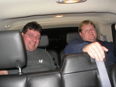 [Joe and Kurt crammed into the back of a sport utility vehicle]