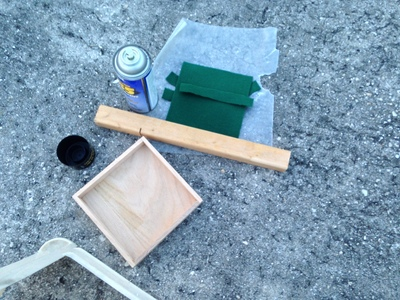 [Wax paper to keep the felt off the asphalt, and a scrap piece of wood to keep the wax paper on the asphalt.]